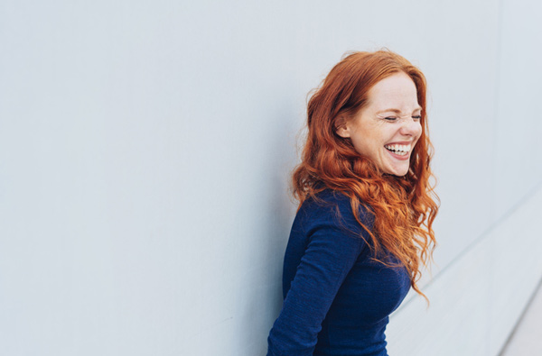 Woman leaning againtst wall and smiling
